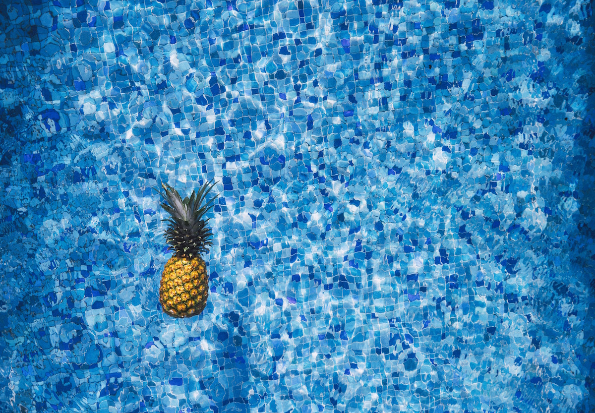 A pineapple floats in a bright blue swimming pool.