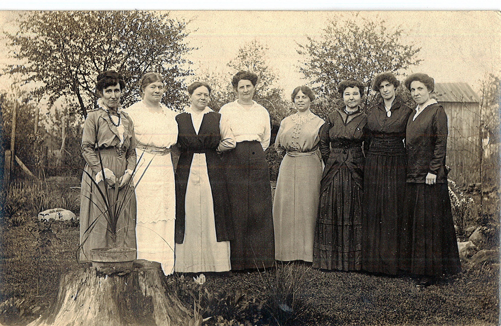 An old, black and white photo of a group of women standing together outdoors, in front of a backdrop of trees - from the Kalamazoo Public Library McConnell collection