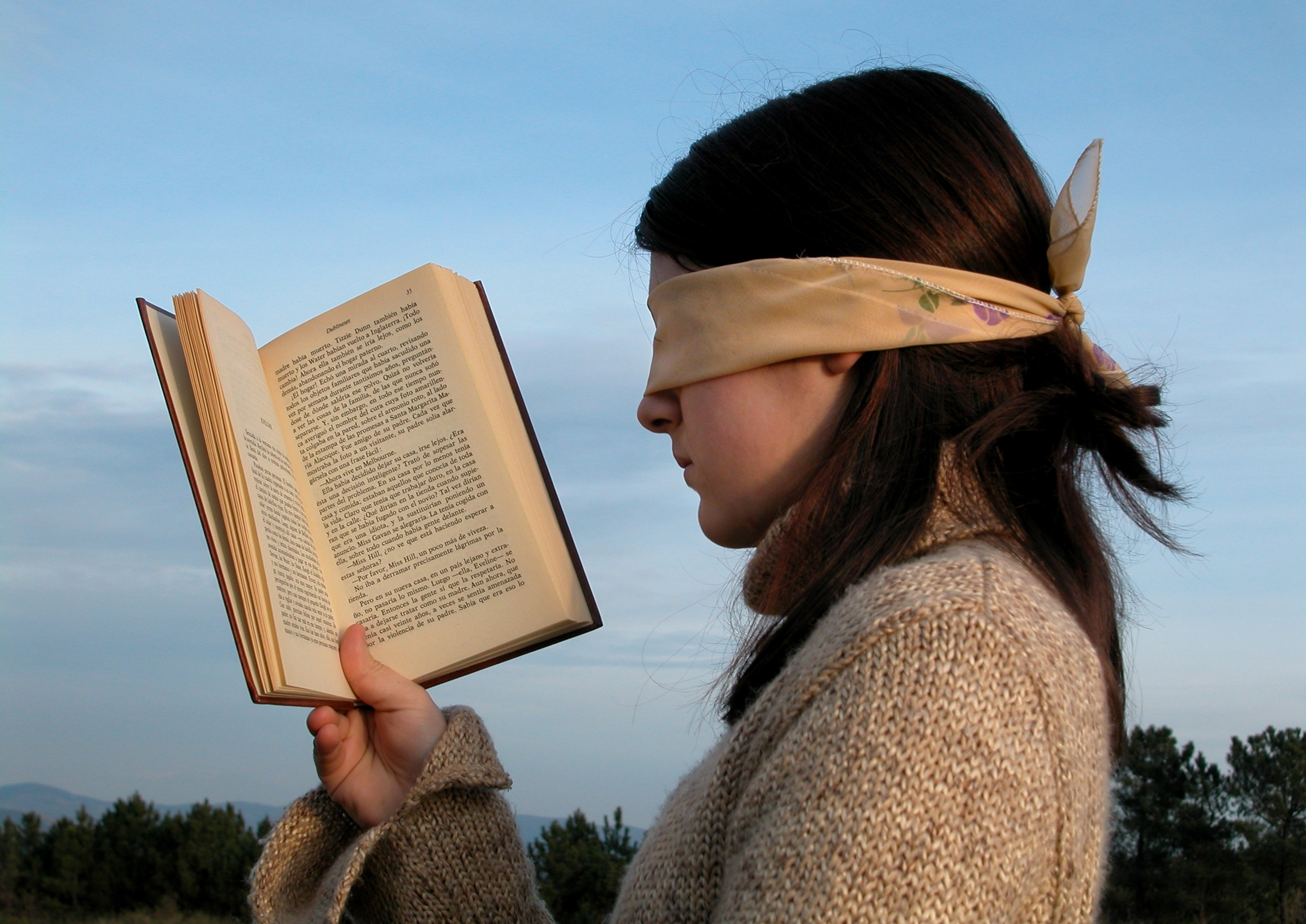 A woman is wearing a blindfold and holding up a book as if she is reading it.