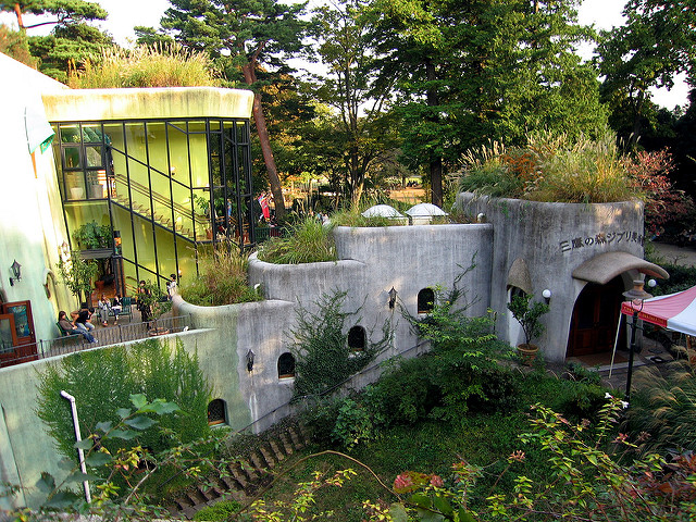 An external shot of the Studio Ghibli museum in Japan, a grey concrete building covered in green vines.