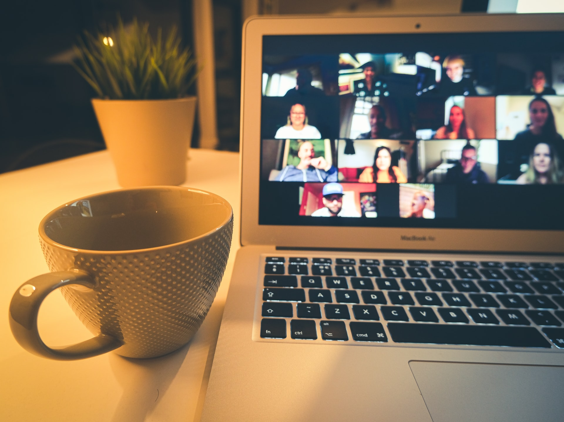 a laptop showing a zoom chat with a coffee cup next to it