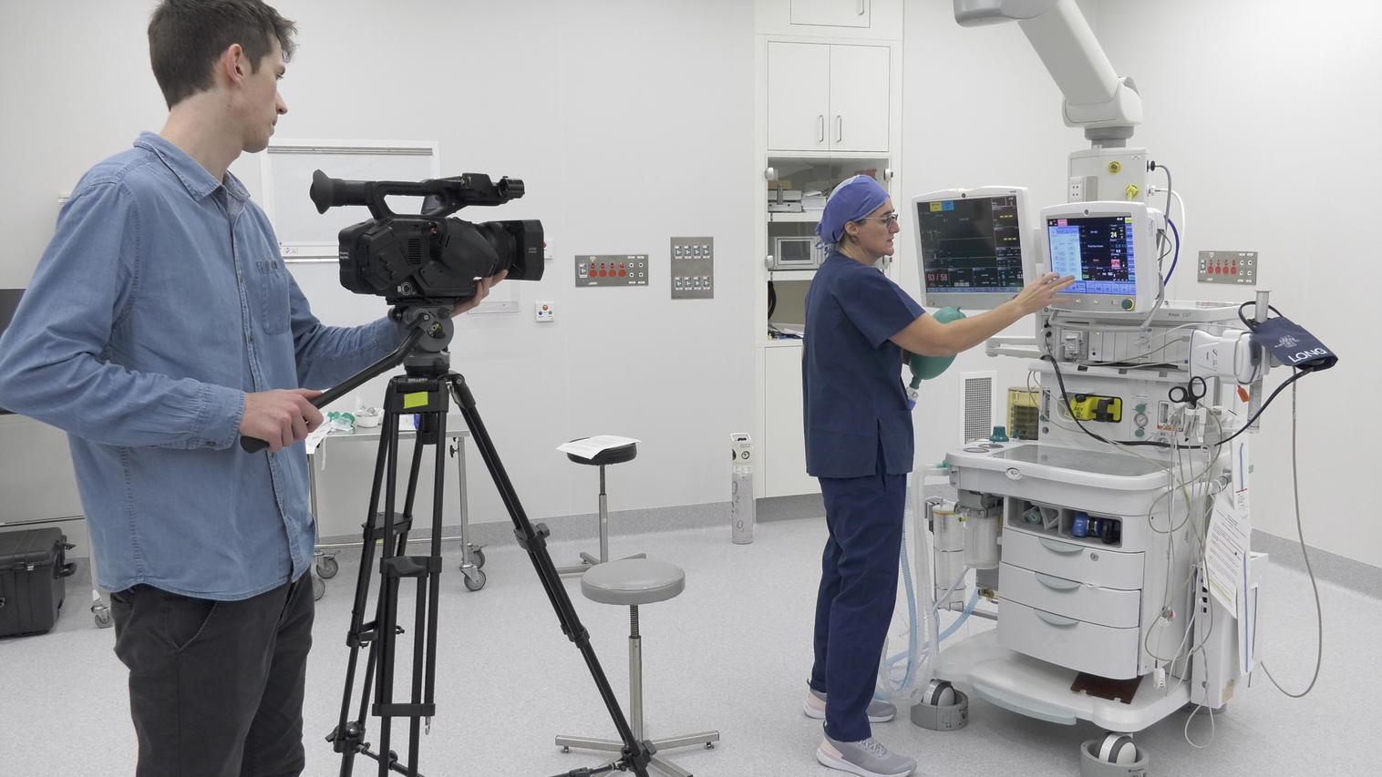 a cameraman films a doctor at work, checking a machine