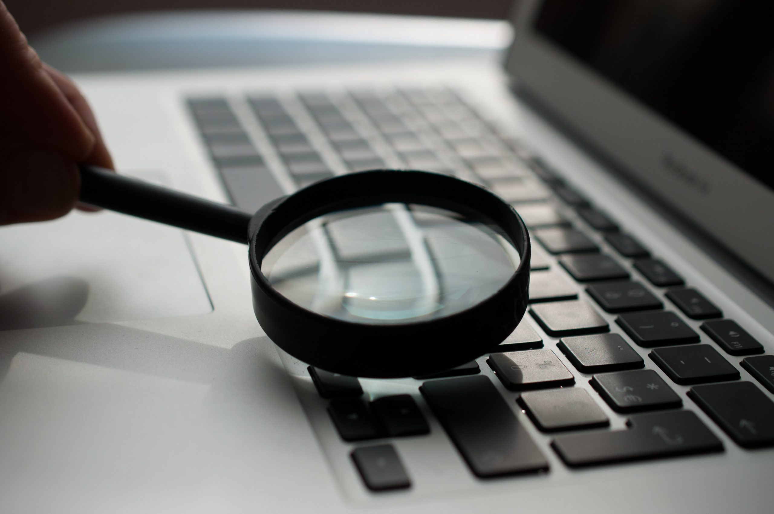 A detective's magnify glass ontop of a laptop