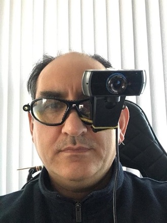 a man with a webcam attached to his glasses, covering one eye