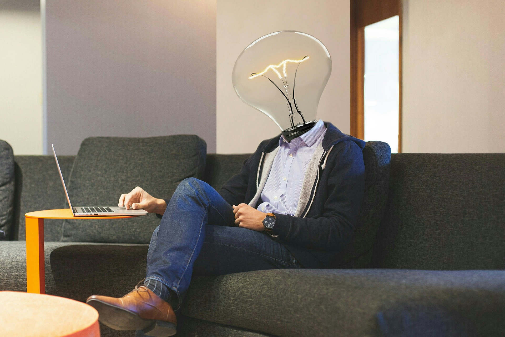 a man sitting on a sofa using a laptop. Instead of a head, there is a lightbulb atop his neck